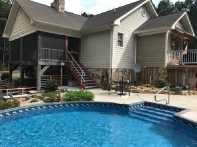 Freedom above ground pool installed completely inground with liner stair, center hand rail, and concrete deck