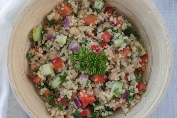 Bulgurový salát s okurkou, paprikou, cizrnou a cibulkou ochucený olivovým olejem s česnekem, citronovou šťávou a bylinkami je osvěžující letní pokrm.