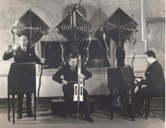 """'The Theremin Electro Ensemble' later called 'The Electrio' in 1932. (Left)Playing the RCA theremin is Leon Theremin's assistant, Julius Goldberg (with customised """"lightning bolt"""" art deco, brass nickel chrome antennas). (Centre) playing the """"Theremin Cello"""" is the Leonid Bolotine and (Right) Pianist Gleb Yellin is playing a Theremin Keyboard. In 1932, the ensemble could be heard on the radio every Monday afternoon at 2:15 over the Columbia Network, KMBC. (2)"""