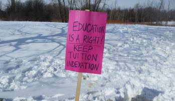 """A pink sign in the snow reads """"Education is a right! Keep tuition indexation""""."""
