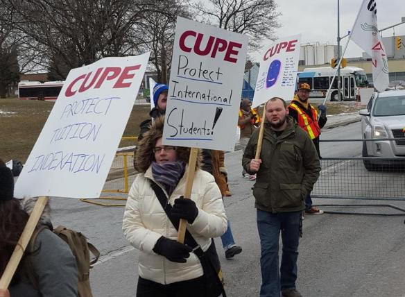 """A member carries a sign saying """"protect international students"""" at the January 20th rally."""