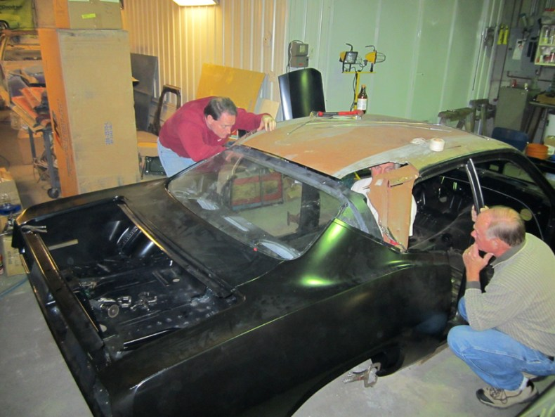 "Bill Embree (knelling at the passenger side door opening) helping to access the ""squaring"" of the Body Panels"