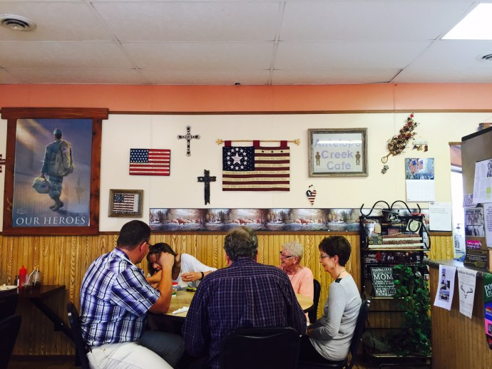 wall with flags, crosses and poster with family eating