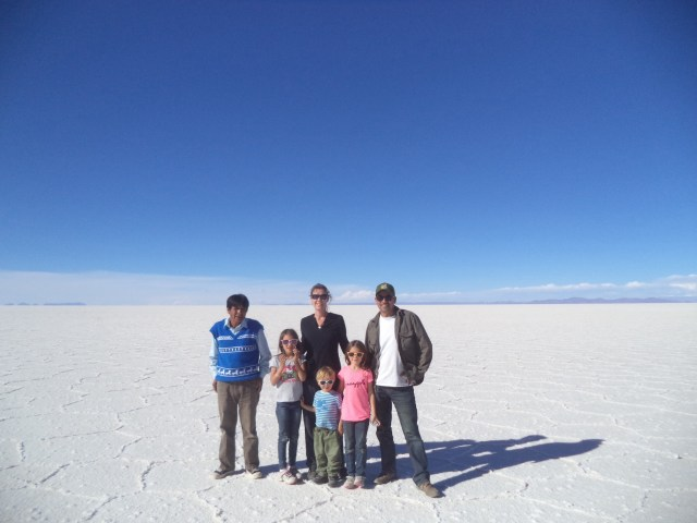 Salar de Uyuni. Family pic with Bernado our driver for the day (with a mouth full of coco leaves).