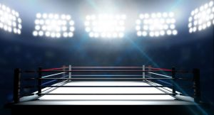 36164654 - an boxing ring surrounded by ropes spotlit by floodlights in an arena setting at night
