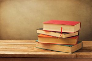 39478497 - vintage old books on wooden deck tabletop against grunge wall