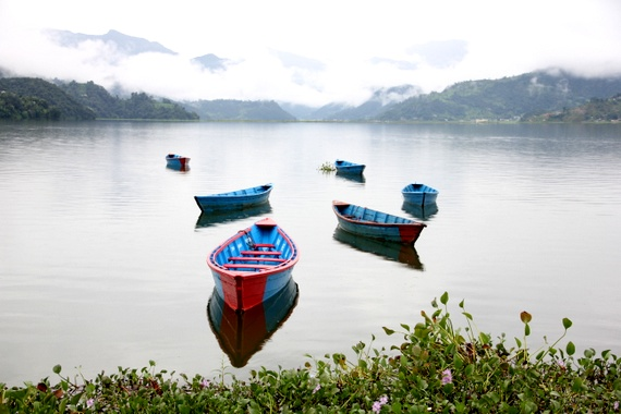pokhara rowboats on lake below Himalayas