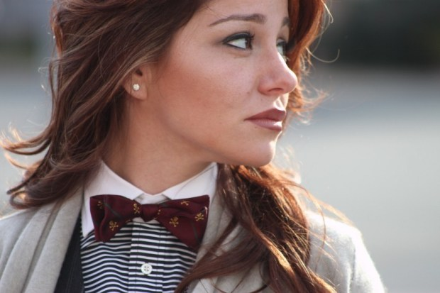 Girl looking away from camera wearing a maroon bow tie