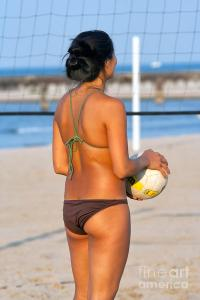 Girl on the beach playing volleyball