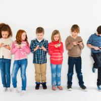 Children using smartphones, standing in a row