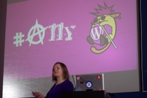 Rian Rietveld speaking in front a slide with a punk wapuu and #A11Y in a anarchy/punk font