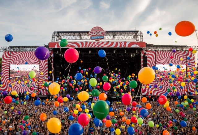 Drone photo of a large stage with colorful balloons floating to the sky