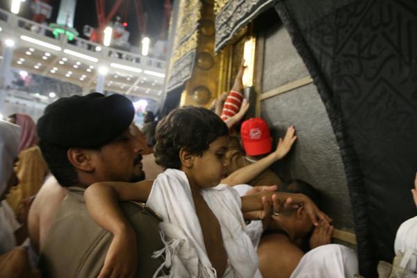 رجل أمن في المسجد الحرام مع أحد المعتمرين الصغار بأنه مكنه من الوصول للكعبة وسط الزحام الشديد.