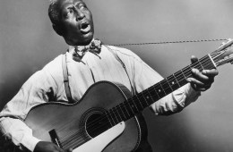 circa 1935:  Promotional portrait of American blues musician Huddie 'Leadbelly' Ledbetter (1889 - 1949) playing a 12-string guitar and singing.  (Photo by Hulton Archive/Getty Images)