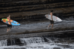 Surfers Get Smashed Off Rocks by Incoming Wave