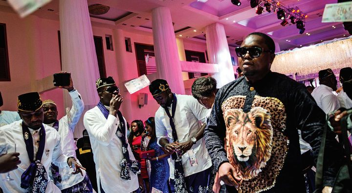 """A posh wedding in Lekki filled with guests from the music and film industries and complete with """"spraying""""— throwing money in the air in the bride and groom's direction."""