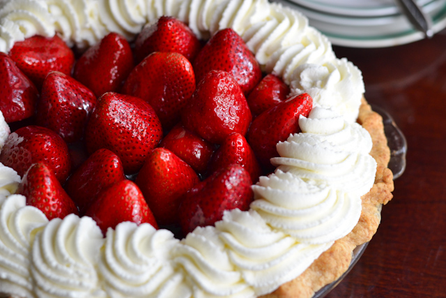 A luscious summer pie filled with fresh strawberries and crowned with whipped cream.