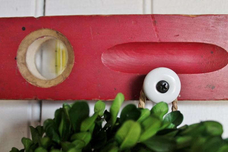 Close up of white ceramic knob on red vintage level