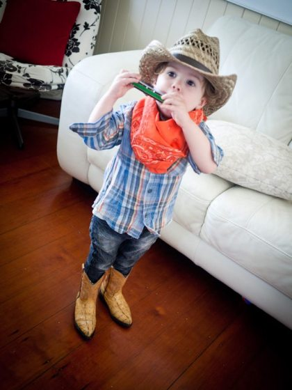 toddler in a cowboy hat playing harmonica