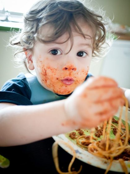 toddler with spaghetti face