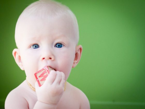 blue eyed baby with green background