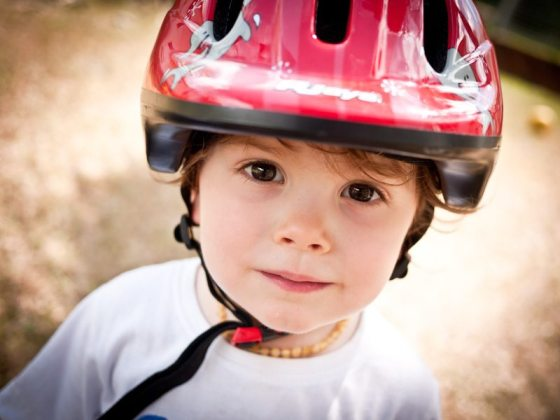 little boy with a red bicycle helmet