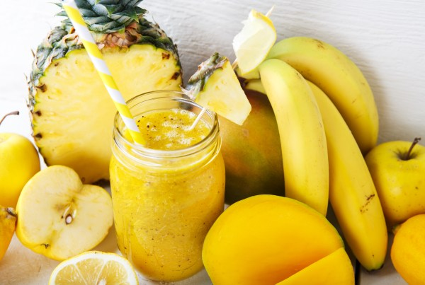 Fresh organic yellow smoothie with banana apple mango pear pineapple and lemon as healthy drink