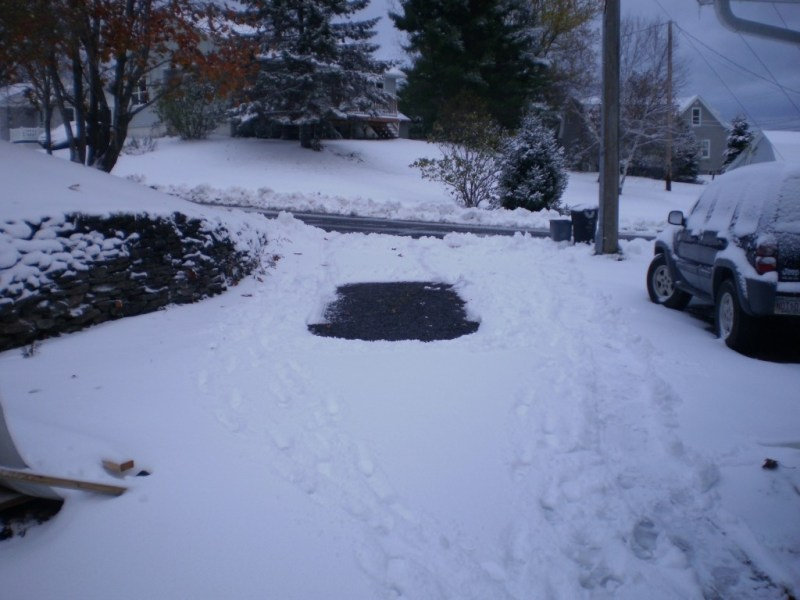 Snow, driveway, footprints, drag mark where the garbage can went.