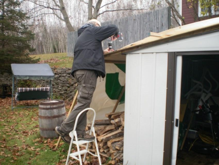 Strange Man screwing plywood onto frame.