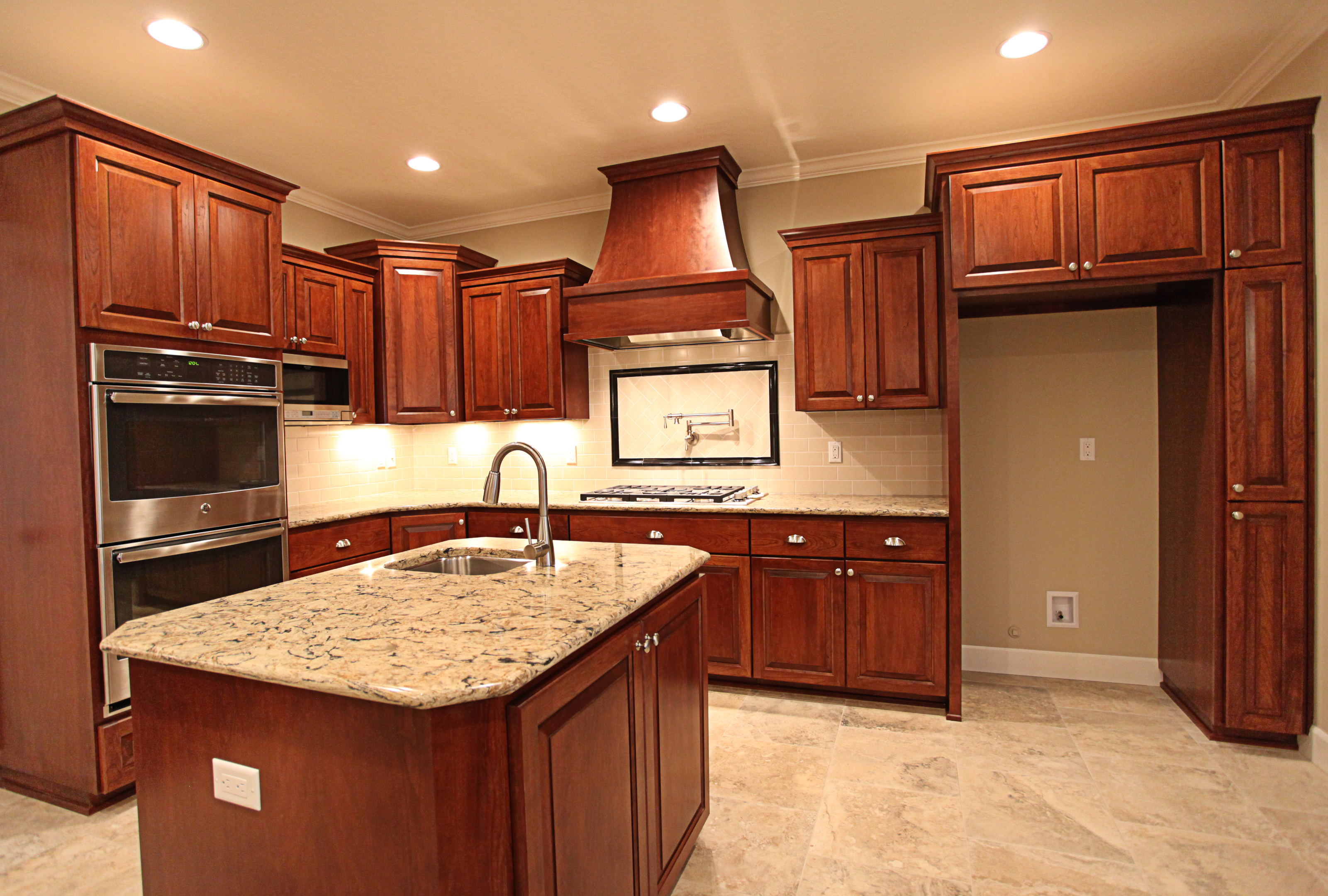 Kitchen  traditional style  cherry  dark color  raised panel  wood hood  micro in upper  staggered heights  small sink in island  narrow pantry cabinet   13 crown