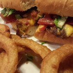 Cheesesteak sandwich with grilled onions, red bell peppers, American cheese, lettuce and tomato.  Side of onion rings.  (Photo Credit: Adroit Ideals)