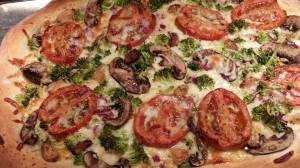 Tomato, mushroom, and broccoli pizza with roasted garlic cloves  (Photo Credit: Adroit Ideals)
