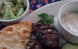 Serve the grilled lamb meatball patties with a cucumber Greek yogurt sauce and a cool lemony cucumber dill salad. (Photo Credit: Adroit Ideals)