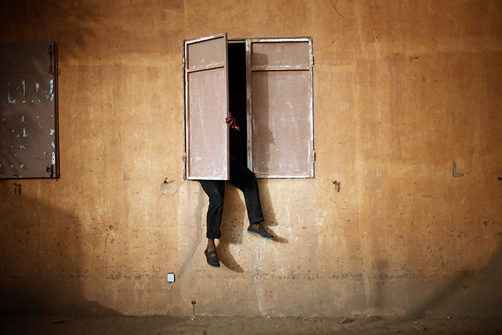 A Malian man sits on a window sill to watch the African Cup of Nations