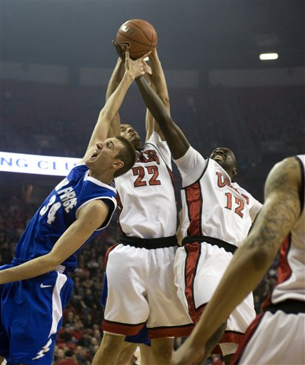 UNLV's Chace Stanback (22) and Brice Massamba battle for a rebound with Air Force's Taylor Broekhuis in the first half. (AP Photo/Las Vegas Review-Journal, K.M. Cannon)
