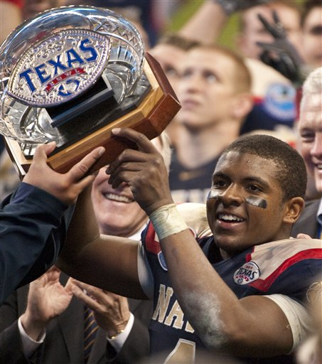 Navy quarterback Ricky Dobbs hoists the Texas Bowl trophy after the Midshipmen's 35-13 win against Missouri. (AP Photo/Dave Einsel)