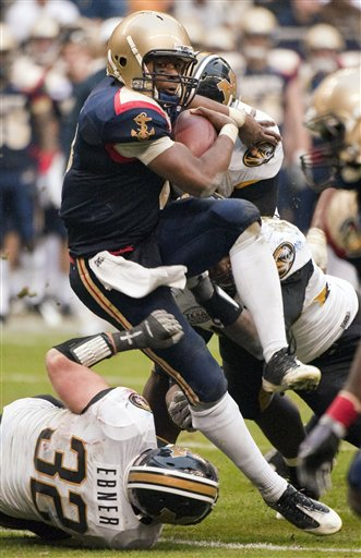Navy quarterback Ricky Dobbs runs over Missouri's Will Ebner (32) for a first down during the third quarter of the Texas Bowl. (AP Photo/Dave Einsel)