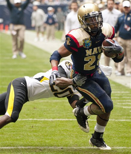 Navy's Marcus Curry runs fo nine yards as Missouri's Kevin Rutland attempts to bring him down in the first quarter of the Texas Bowl. (AP Photo/Dave Einsel)