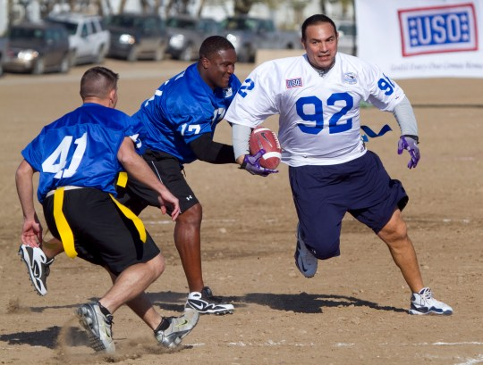 """Football legend Tony Casillas (92), playing for Team Freedom, tries to evade Team Liberty's Spc. Aaron Decker, (41) of Marshfield, Wis., and college quarterback legend Tee Martin, who were playing defense during the first-ever Tostitos """"Salute the Troops"""" Bowl in Baghdad, Iraq, on Jan. 1, 2010."""