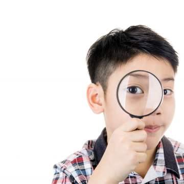Myopia: little boy looks through magnifying glass