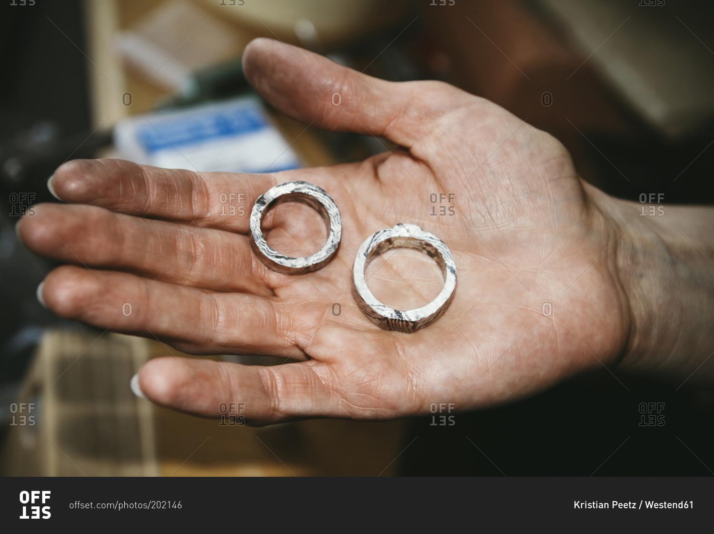 goldsmith working on wedding rings in mokume gane style hand holding mokume gane wedding bands Goldsmith working on wedding rings in Mokume Gane style hand holding unfinished ring