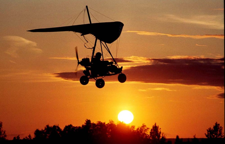 Ultralight taking off with sun on the horizon