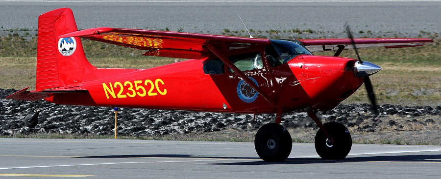 Red Cessna 180 on a take off roll