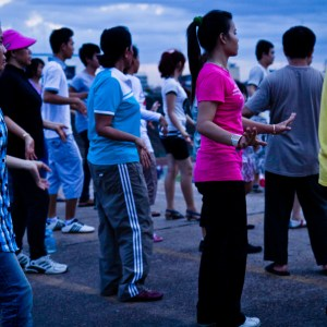 Every evening around the rim of Olympic Stadium in Phnom Penh, locals gather for their evening aerobics workout. Circling the stadium, instructors spread out with battery powered sound systems and call instructions out to their assembled crowd.