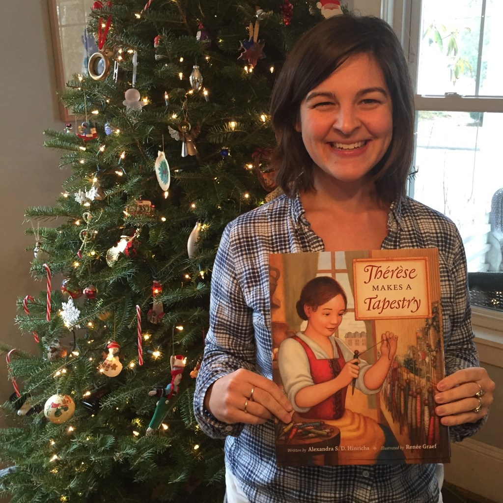Photo of Alexandra S. D. Hinrichs holding her first book, Thérèse Makes A Tapestry