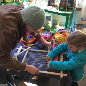 """photo of young girl weaving at book launch for """"Thérèse Makes a Tapestry"""""""
