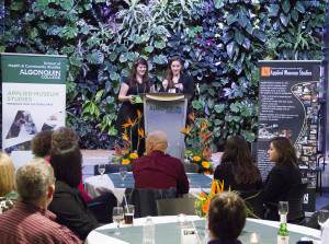 Co-emcees, third-year students Kristen Stanley and Kristie Bredfeldt, welcome alumni, staff, students and cultural industry partners at the Applied Museum Studies fortieth anniversary celebration on Nov. 16, 2013.  Photo courtesy of first-year photography student Marc Brigden.