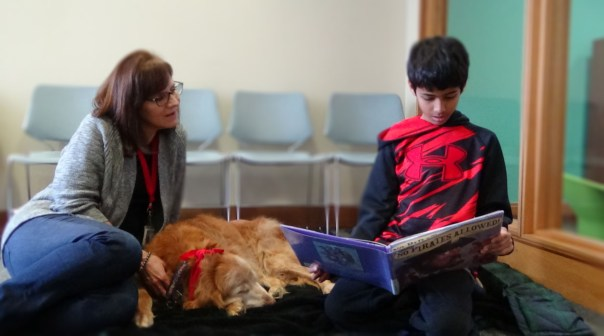 Naj Nalik, 9 years old, reading his second book to Sedona during his therapy session while Sedona's owner, Cathy Maher looks on. (Photo: Alicia Buster/Full Sail University)