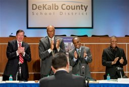 Dekalb County school Superintendent Michael Thurmond, center right, and chairman Melvin Johnson, center left, applaud along with board member James McMahan, left, and Stone Mountain High School student DeMarco Poole, right, after Southern Association of Colleges and Schools CEO Mark Elgart, foreground, announced the school district has been removed from probation, Tuesday, Jan. 21, 2014, in Stone Mountain, Ga. Georgia's third-largest school district has been moved off probation for its accreditation, after a tumultuous few years that included the rare step of the governor removing a majority of the local school board. Officials with the Southern Association of Colleges and Schools made the announcement Tuesday during a packed school board meeting in DeKalb County. The metro Atlanta school district serves nearly 100,000 students. (AP Photo/David Goldman)