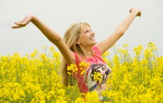 happy blond girl with open arms enjoying and smiling at the sky